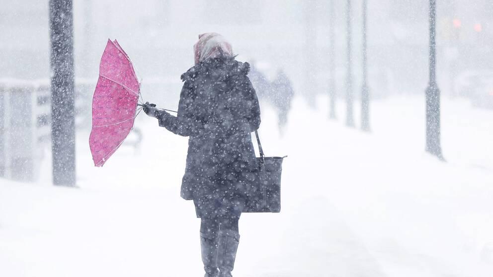 Kvinna med paraply mot snön
