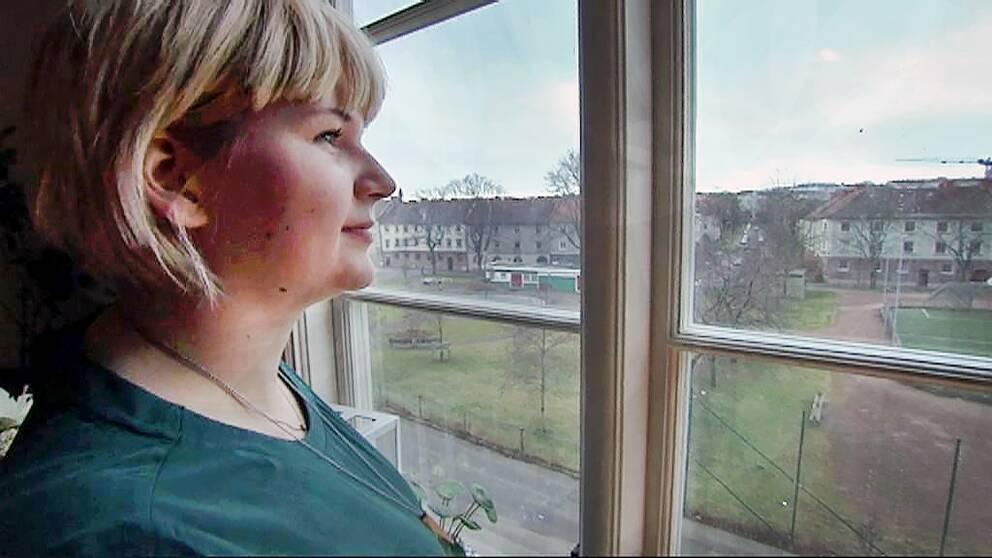 Liza Eklund tittar ut genom ett fönster.