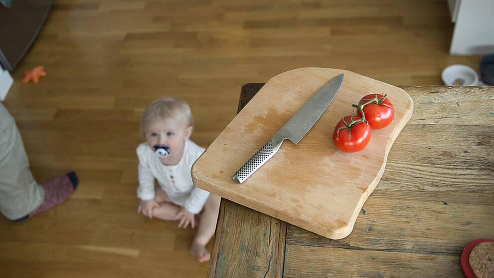 Faror i hemmet för små barn. En bebis riskerar att få tag på en vass kniv hemma i köket.