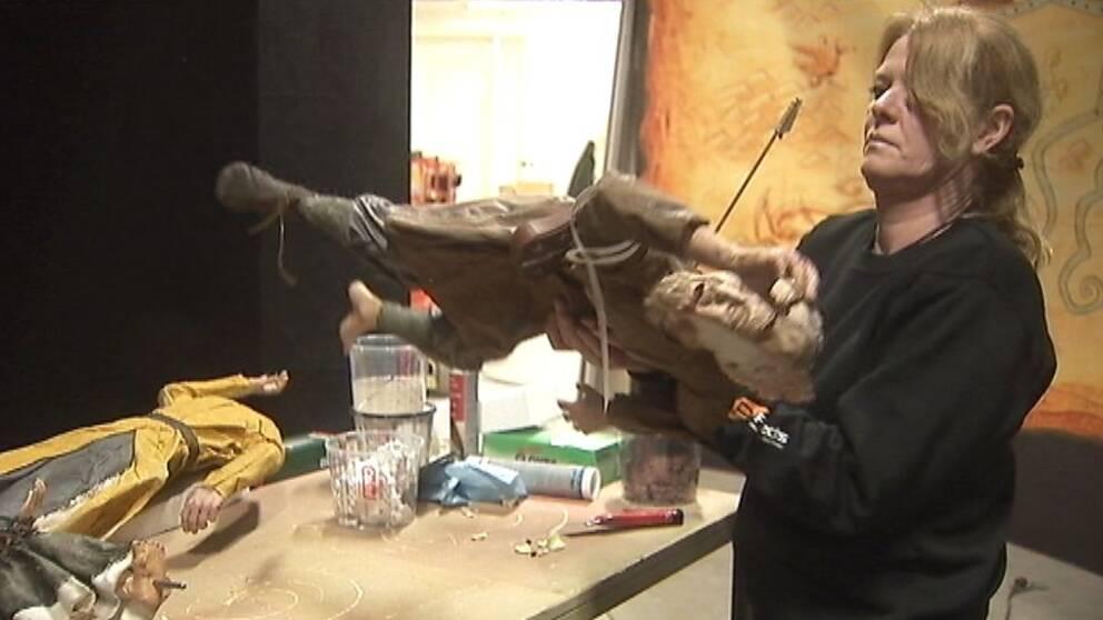 en kvinna som håller en docka som har en pil genom ryggen. Dockan har tidstypiska kläder från vikingatiden.