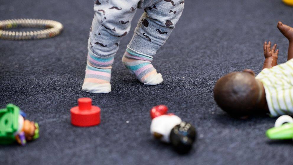 Barn i förskolan, närbild på ett barns ben och en docka.