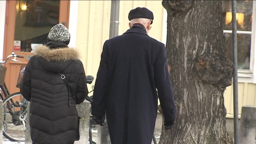 ryggtavlor på två pensionärer som promenerar