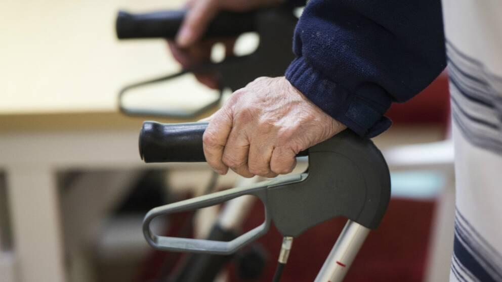 Arkivbild på äldre man med rullator.