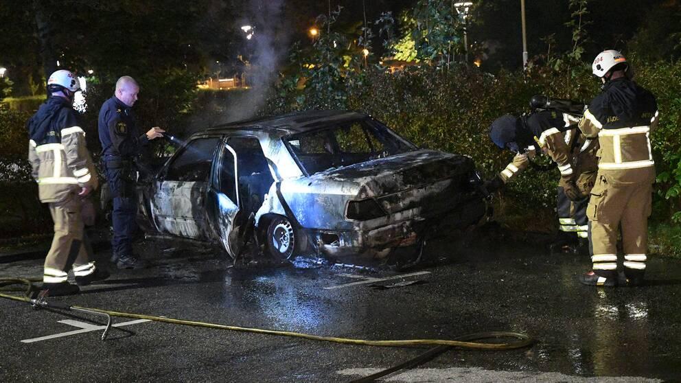 Räddningstjänst och polis kontrollerar en utbränd bil på Kärleksvägen i Burlöv.