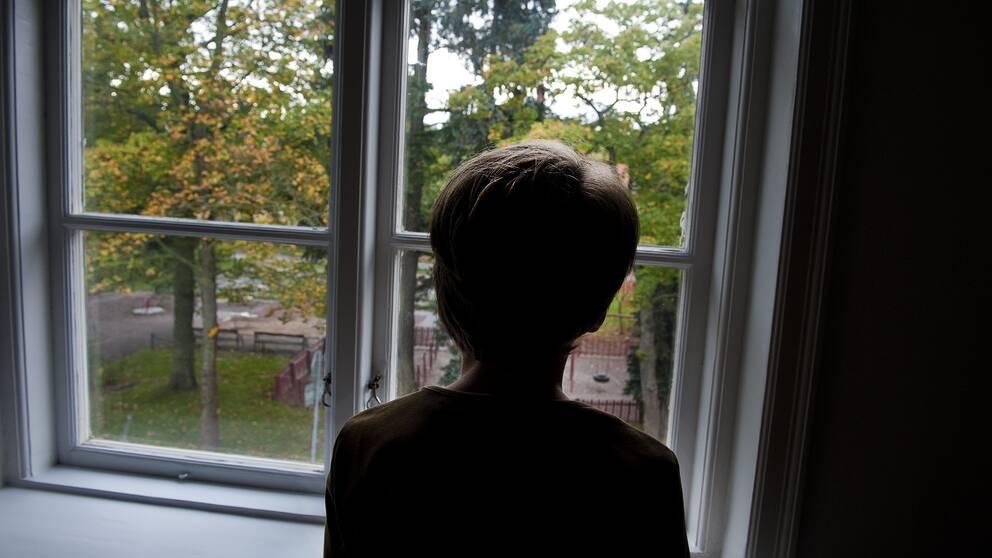 Ensam pojke vid ett fönster.