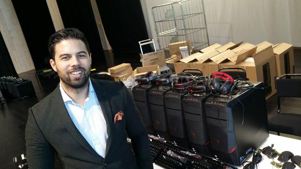 Tommy Ingemarsson är världsmästare i CS och går under aliaset Potti. Här står han leendes i kavaj intill en mängd datorutrustning.