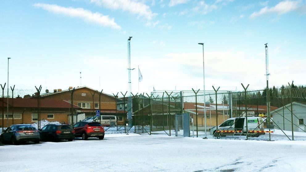 parkerade bilar på snöig plan utanför fängelsets stängsel