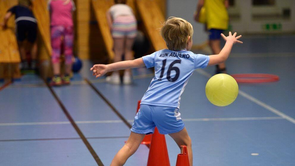 Pojke spelar boll under idrottslektion