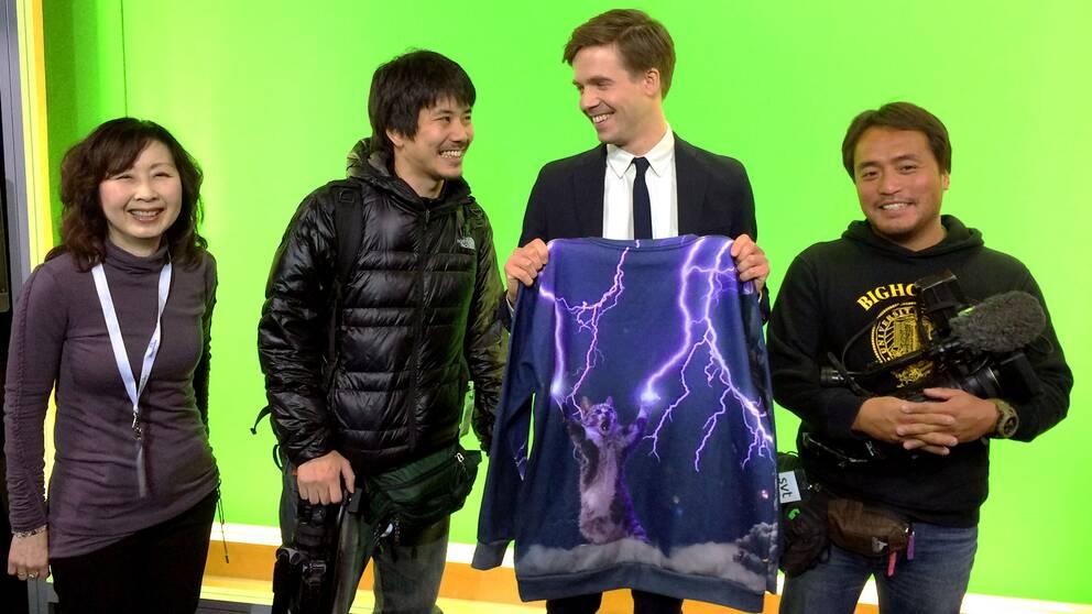 Översättaren Takako Makino (t.v.) tillsammans med SVT:s meteorolog Nils Holmqvist och hans världskända tröja. Reportern Shohei Umemura och fotografen Mutsuaki Kiyohara från TV Tokyo tog sig till SVT-huset just på grund av den klassiska kattröjan.