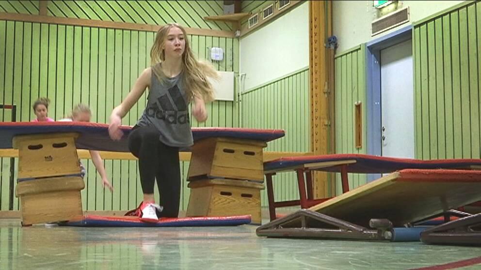 En elev har krupit under ett hinder gjort av plintar och madrasser i en gymnastiksal.