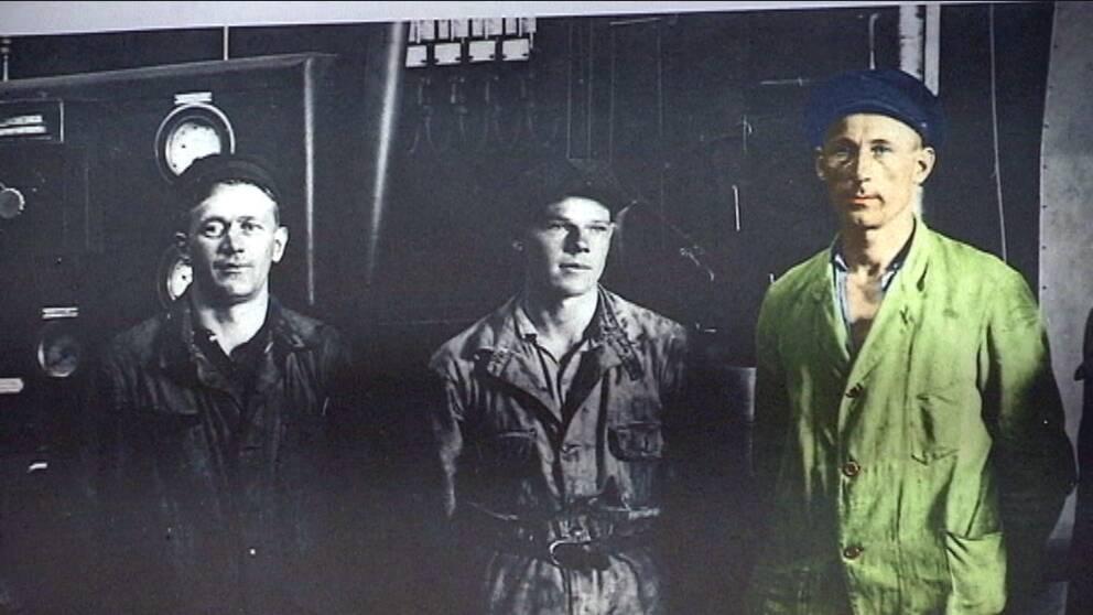 Tre män i arbetskläder på ångkraftverket