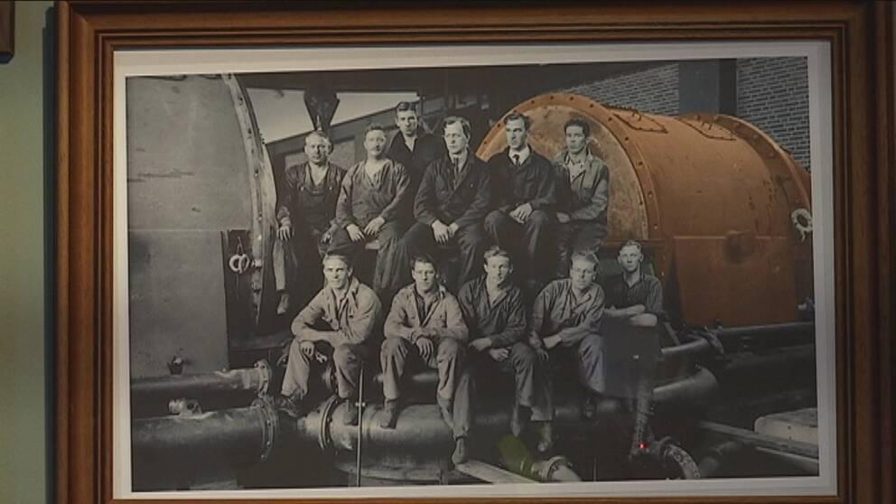 11 män poserar framför en stor generator
