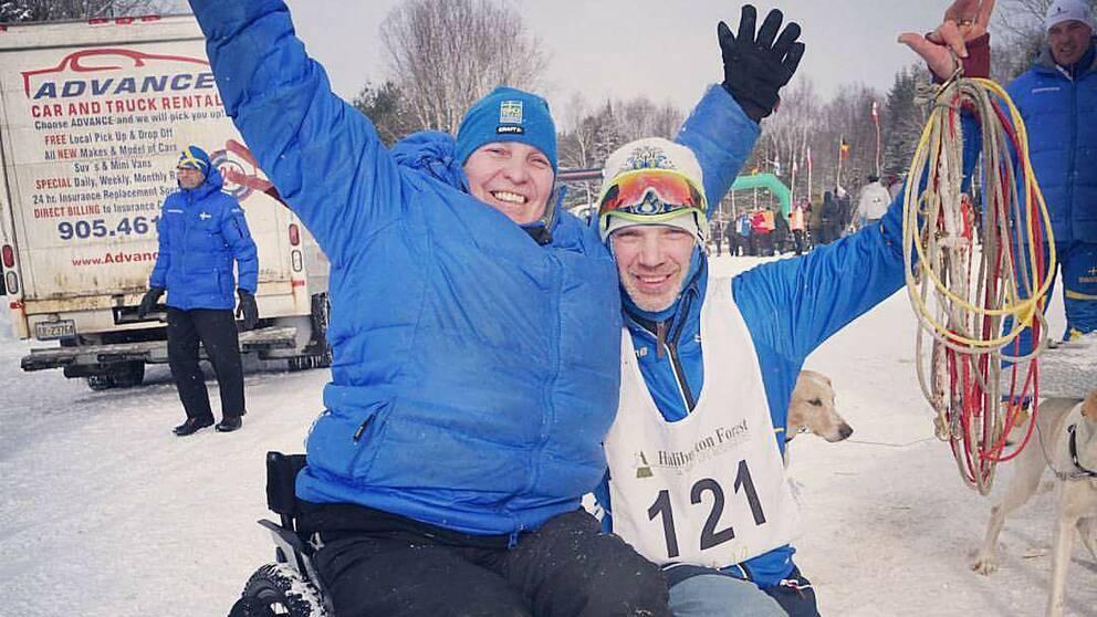 Lycklig draghundperson och en kvinna i rullstol