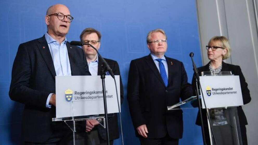 En man med glasögon bakom ett talarpodium pratar på en presskonferens, två män och en kvinna står lite bakom honom.