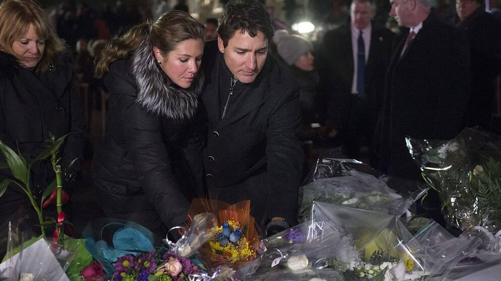 Premiärminister Justin Trudeau tillsammans med hustrun Sophie lägger ned blommor under en minnesstund i Québec.