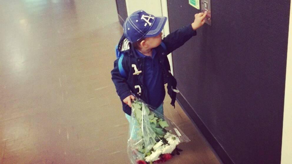 Pojke med blommor trycker på hissknappen