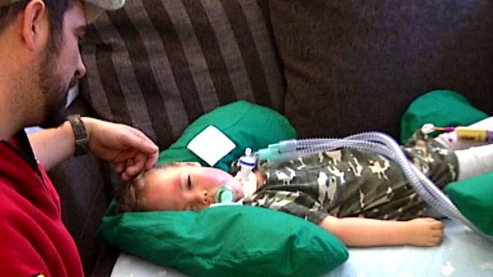 Amadeus, 2, från Edsvalla ligger på soffan, pappa sitter bredvid