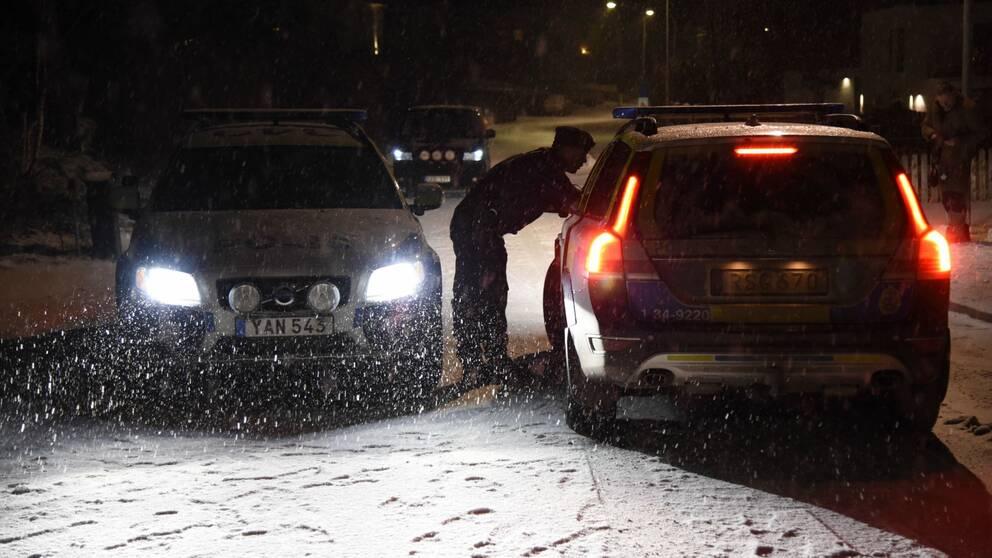 Två polisbilar står på en väg i mörker och snö, en polisman pratar med föraren i ena bilen.