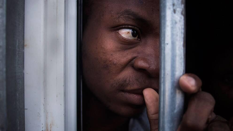En okänd migrant hålls fången i en bur i interneringslägret i Gharyan