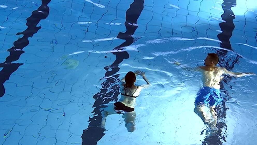 Två personer simmar i en simbassäng.