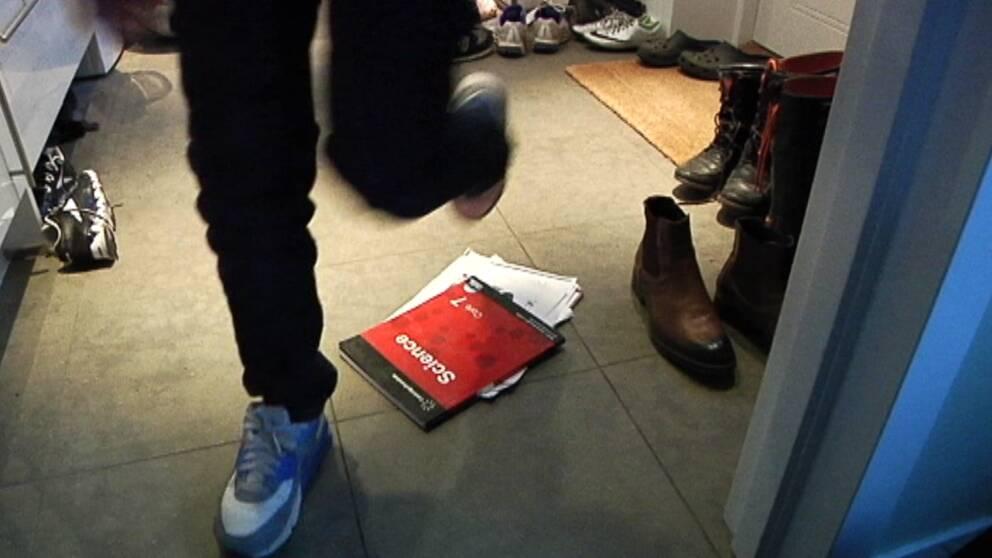 Skolkare, en elevs ben som kliver över skolböcker som ligger på golvet i ett kapprum
