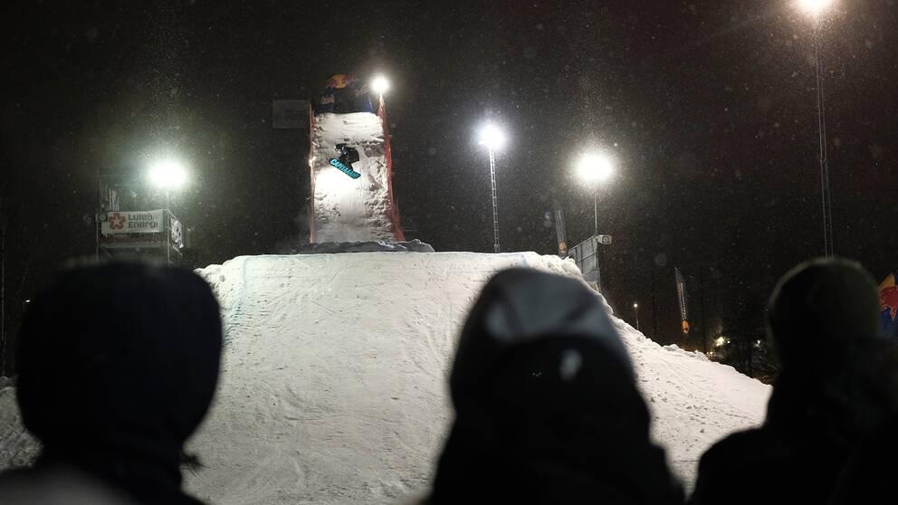 snowboardåkare som hoppar från ramp, åskådare i förgrund