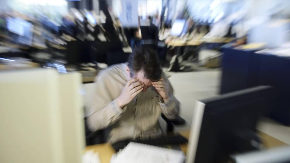 en stressad man i kontorslandskap