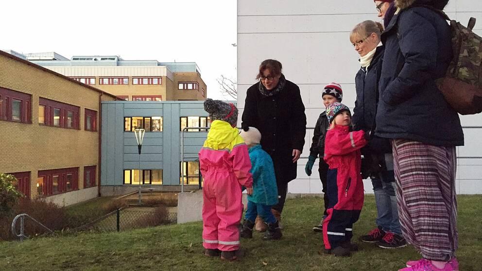 Tre vuxna och fyra barn står tillsammans utanför en vit byggnad.