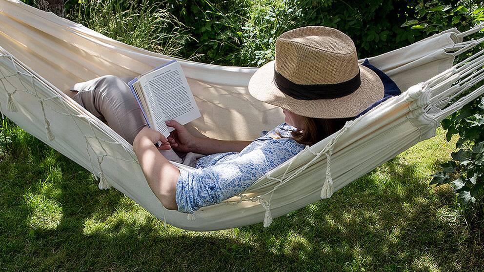Kvinna i hatt, liggande i hängmatta