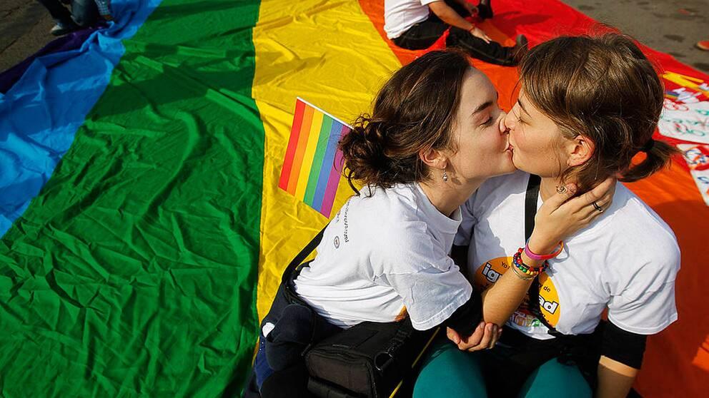 Två unga kvinnor kysser varandra.