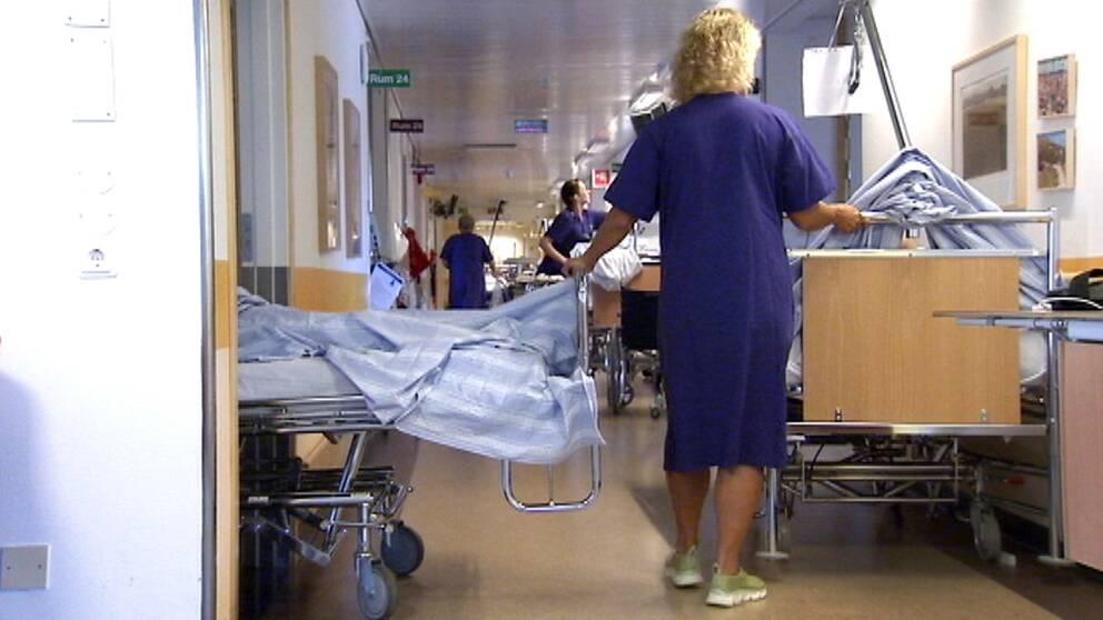 En sjuksköterska flyttar två sängar med patienter i en sjukhuskorridor.