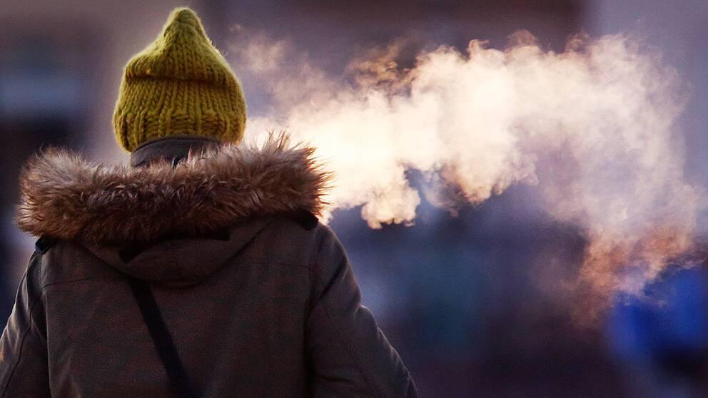 Kallt ute, kvinna med yllemössa bakifrån som andas ut rök i kylan