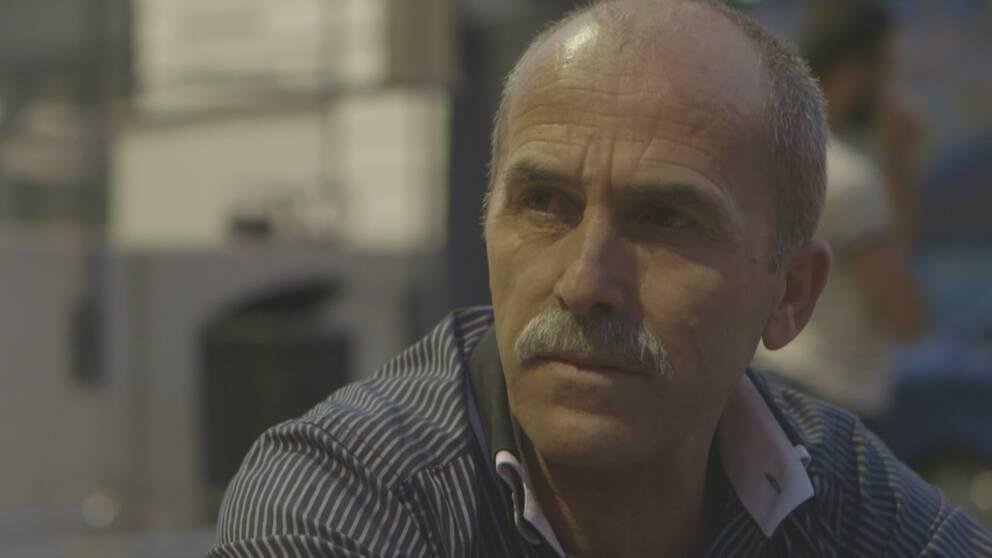 Man med mustasch i blåvitrandig skjorta.