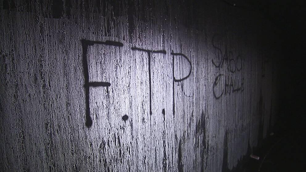 FTP – en förkortning som uttrycker den misstro som många unga i Tensta känner för myndigheterna, klottrat på en vägg i ett utbränt garage.