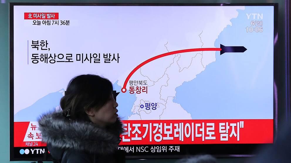 En kvinna passerar framför en tv som visar en grafik över provskjutningen i en nyhetssändning på Seouls centralstation.