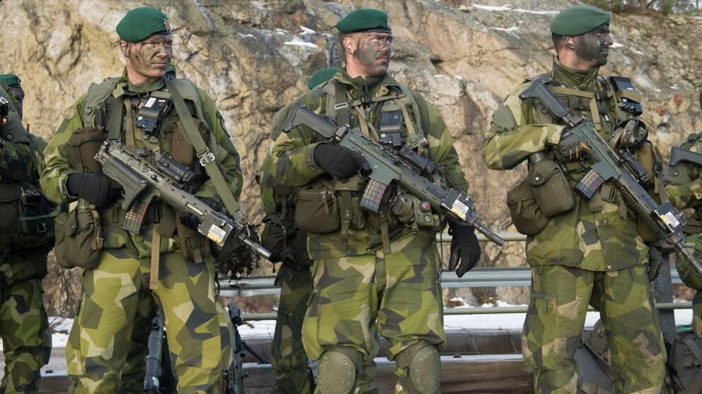 Tre beväpnade militärer med kamoflagemålning i ansiktet