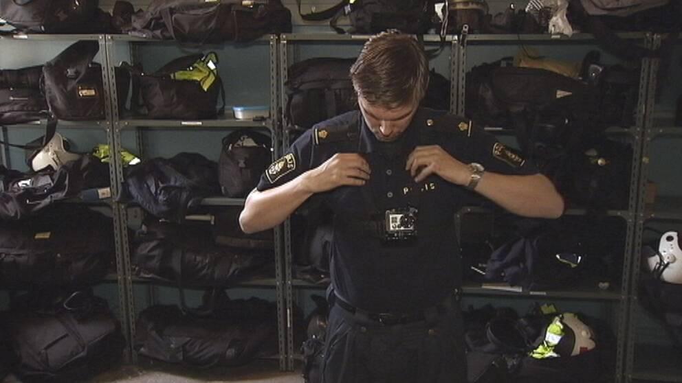 Polisman står i förrådsrum och sätter på sig en kamera på bröstet