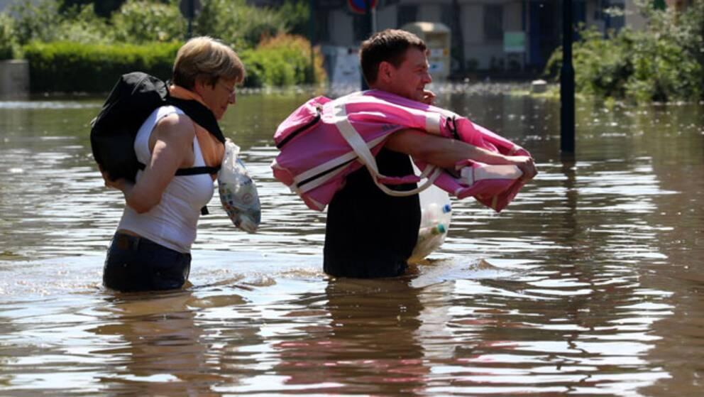 Invånare i Magdeburg i östra Tyskland bär sina tillhörigheter genom de översvämmade områdena runt floden Elbe.