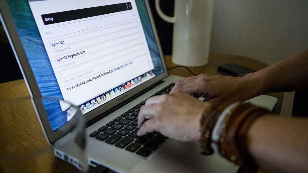 En person knappar på datorn.