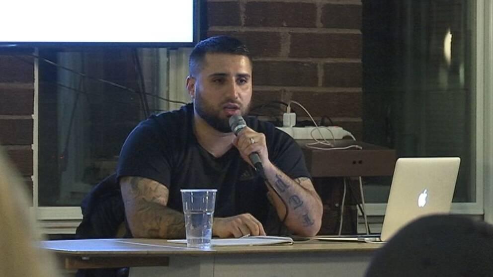 En ung man sitter på ett podie och pratar i mikrofon.