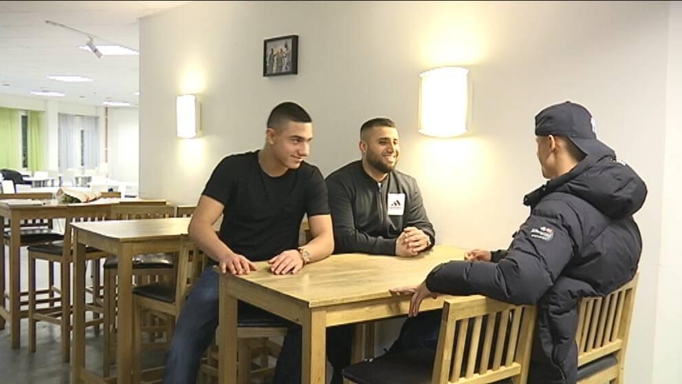Tre unga glada killar sitter runt ett bord och pratar.