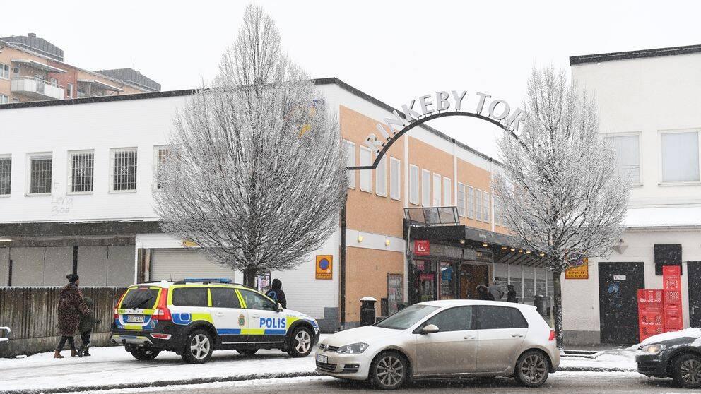Polisbil parkerad vid Rinkeby torg.