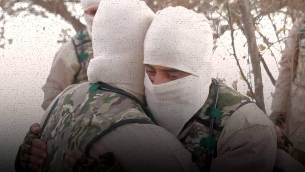Två maskerade män kramas.
