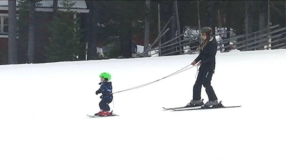 Kvinnan på skidor bromsar ett litet barn som hålls i remma