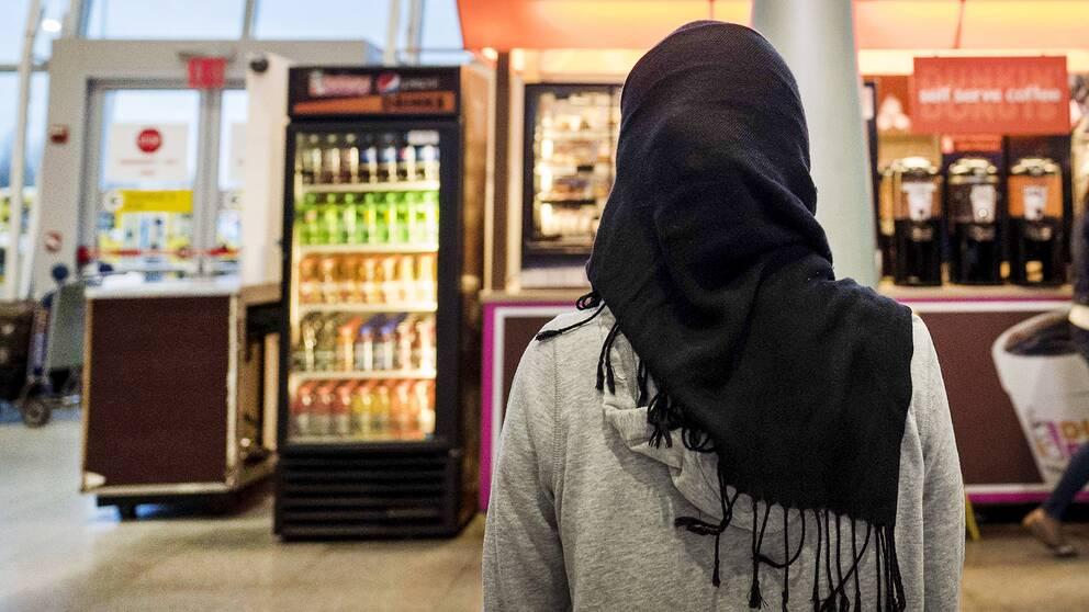 En kvinna med hijab framför ett kafé.