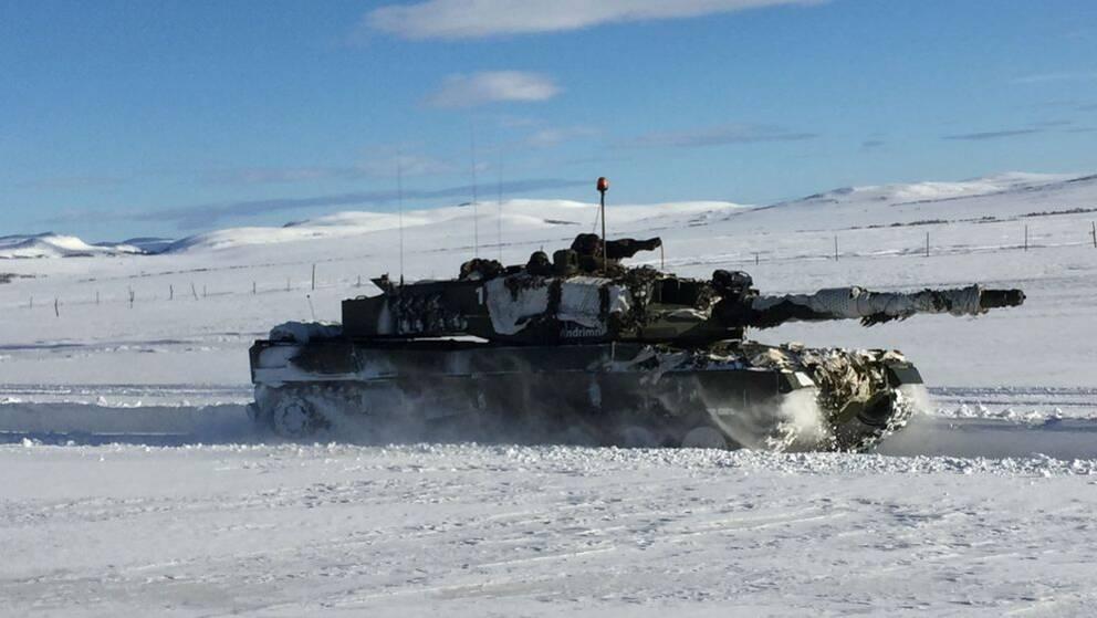 Militärfordon i fjällvärld vinter