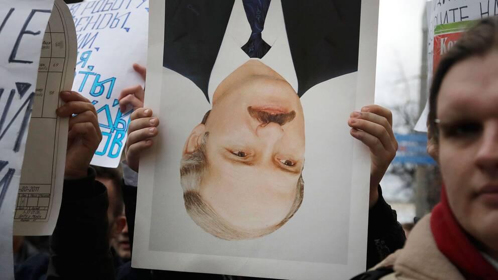 En demonstrant håller ett upp- och nedvänt porträtt av president Aleksandr Lukasjenko, ofta kallad Europas sista diktator, under demonstrationerna i Minsk.