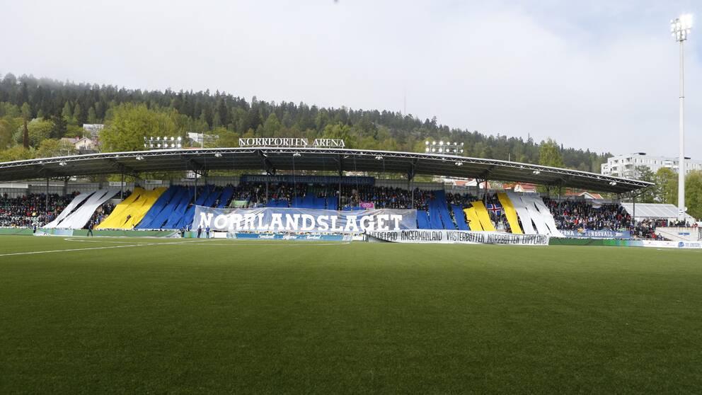 Norrporten arena syns, tillsammans med fotbollssupportrar som håller upp en banner där det står Norrlandslaget.