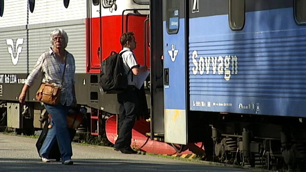 Ett nattåg står inne vid perrong, en man är på väg att kliva på, en kvinna går med väska längs med tåget.