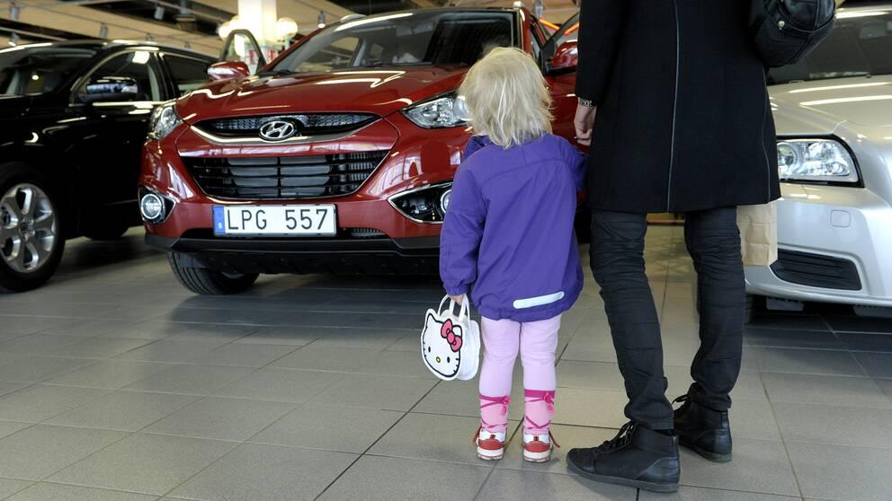 En kvinna kollar på en bil med ett barn.
